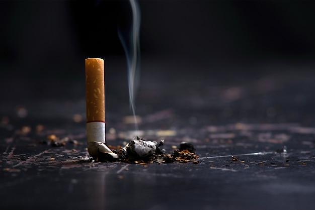 World no tobacco day concept smettere di fumare.accedere il mozzicone di sigaretta sul pavimento Foto Premium