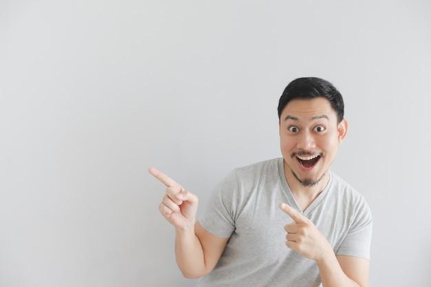Wow e faccia sorpresa dell'uomo in maglietta grigia con punto della mano su spazio vuoto. Foto Premium