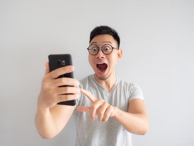 Wow, la faccia dell'uomo ha scioccato quello che vede nello smartphone. Foto Premium