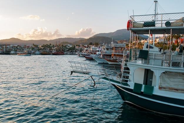 Yacht sul molo sullo sfondo di un bellissimo cielo al tramonto con raggi di sole Foto Premium