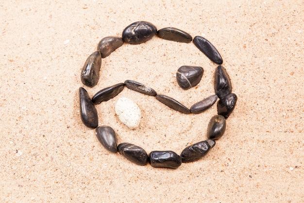 Yin yang disegnato con ciottoli sulla sabbia di una spiaggia Foto Premium