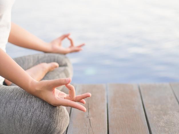 Yoga asiatica della donna del primo piano nel fondo all'aperto Foto Premium