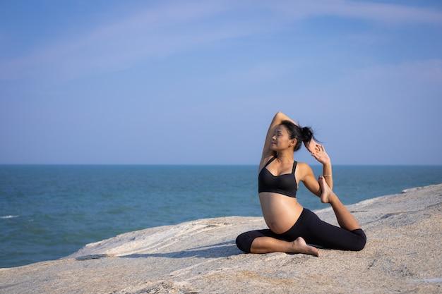 Yoga asiatica della donna incinta sull'ora legale di tramonto della spiaggia Foto Premium