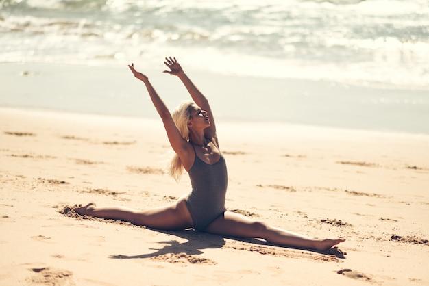 Yoga bionda caucasica di pratica della donna nella spiaggia Foto Premium