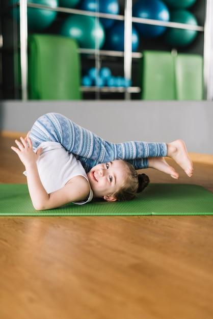 Yoga di pratica della bambina felice sulla stuoia che esamina macchina fotografica Foto Gratuite
