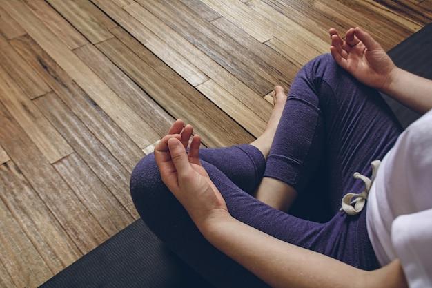 Yoga di pratica della donna che fa posa del loto mezzo con mudra Foto Premium