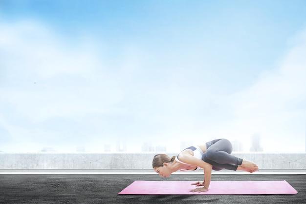Yoga di pratica della donna in buona salute asiatica sul tappeto al fondo del tetto Foto Premium