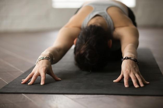 Yoga di pratica della giovane donna attraente posa del bambino Foto Gratuite