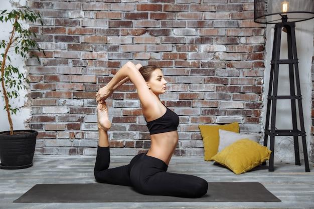 Yoga di pratica della giovane donna attraente Foto Premium