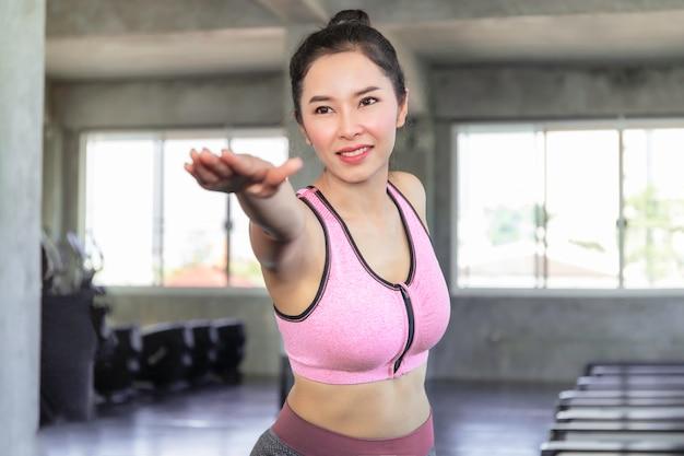 Yoga di pratica della giovane donna dell'asia con il reggiseno e i pantaloni degli abiti sportivi alla palestra di forma fisica. Foto Premium