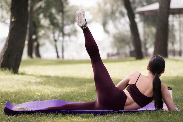Yoga di pratica della giovane donna di vista posteriore all'aperto Foto Gratuite