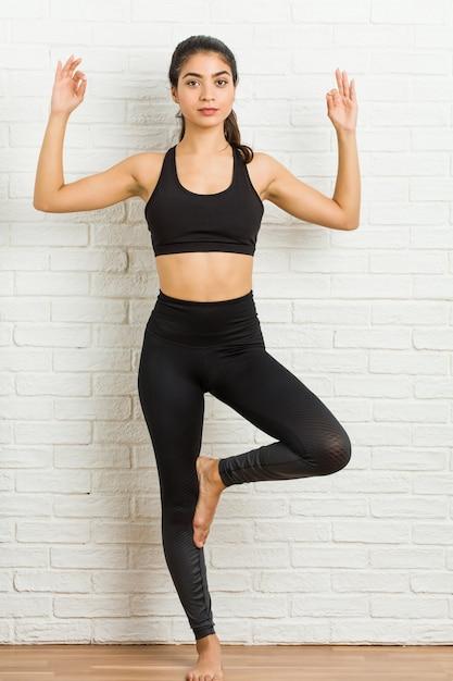 Yoga di pratica della giovane donna sportiva araba Foto Premium