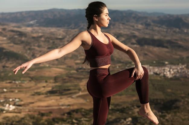 Yoga di pratica femminile giovane di vista frontale Foto Gratuite