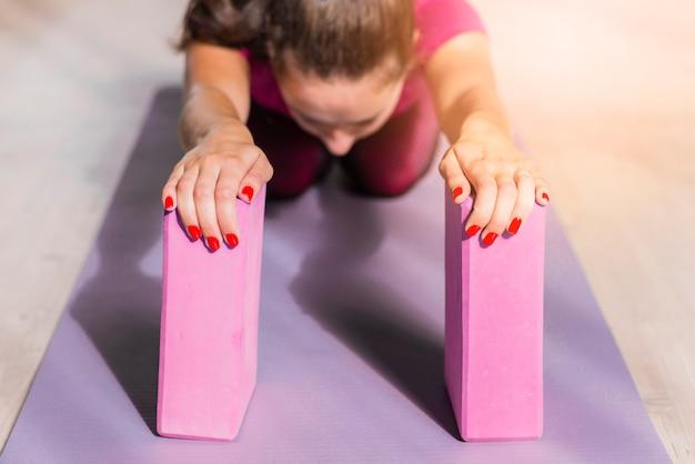 Yoga di pratica sportiva della donna di forma fisica con i blocchetti rosa sul materassino Foto Gratuite