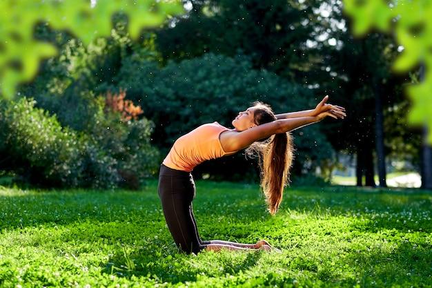 Yoga. yoga di pratica della giovane donna o ballare o allungare in natura al parco. concetto di stile di vita di salute Foto Premium