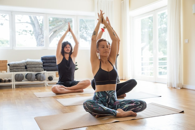 Yogi positivi focalizzati che praticano in palestra Foto Gratuite