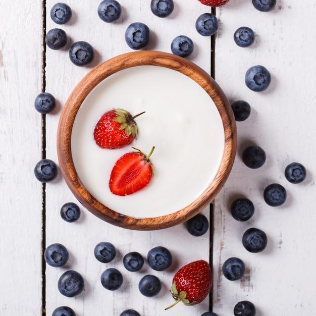 Yogurt fatto in casa, panna acida in una ciotola di frutti di bosco Foto Premium