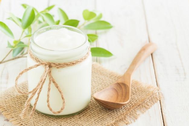 Yogurt in bottiglie di vetro sul tavolo in legno bianco concetto di cibo sano Foto Premium