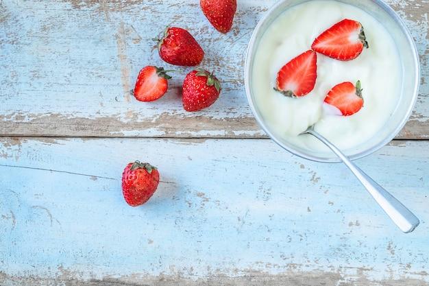 Yogurt naturale e frutta fragola sullo sfondo di legno Foto Premium