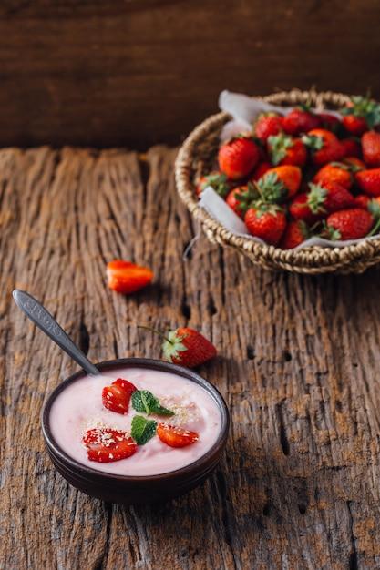 Yogurt strawberry on wooden table background Foto Premium