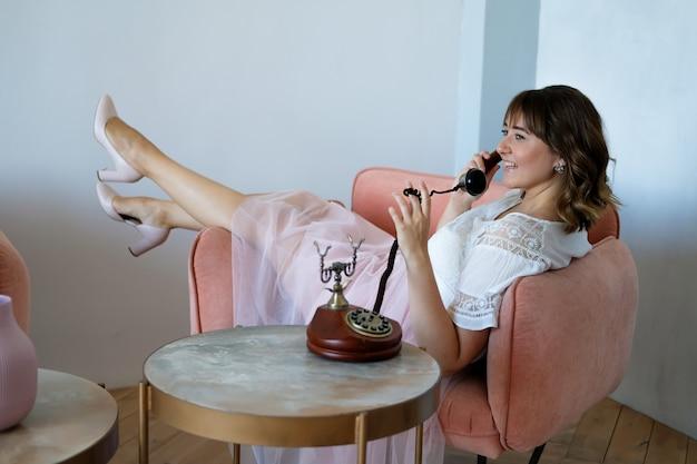 Young plus size donna parlando su un telefono retrò seduto su una sedia primo appuntamento, flirtare Foto Premium