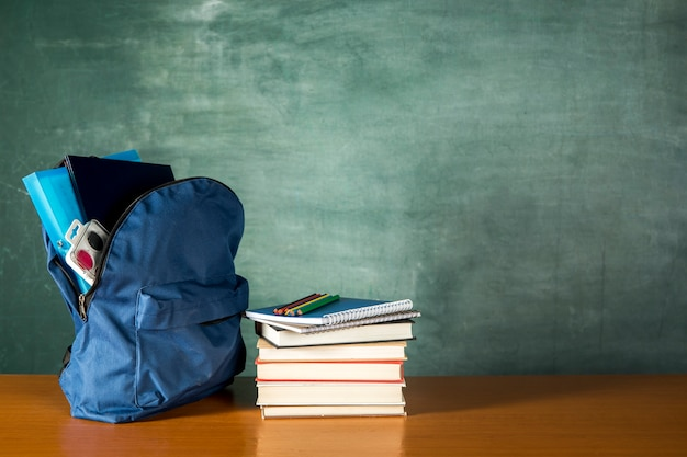 Zaino aperto con una pila di libri Foto Gratuite