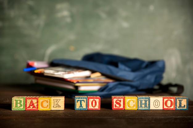Zaino aperto e scritta torna a scuola Foto Gratuite