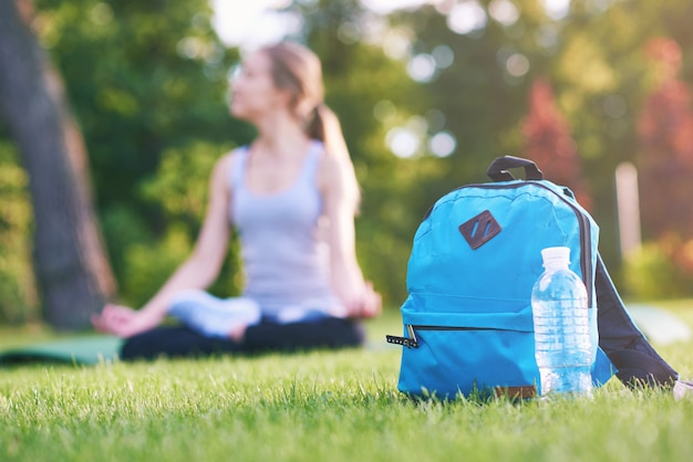 Zaino blu e una bottiglia di acqua nel parco sul copyspace dell'erba Foto Premium