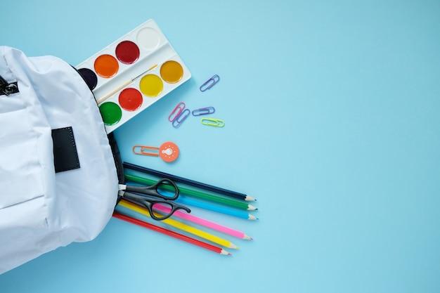 Zaino con diversi elementi decorativi colorati sul tavolo. Foto Premium