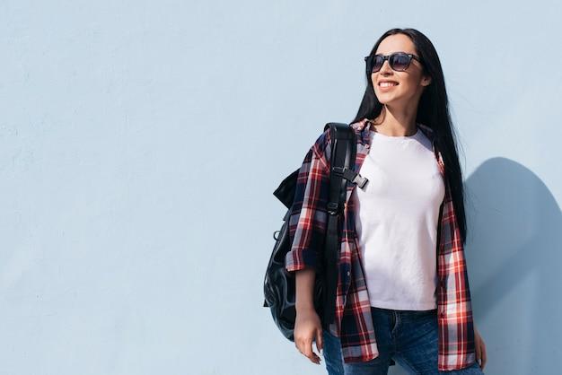 Zaino di trasporto della donna alla moda che posa contro la parete blu Foto Gratuite