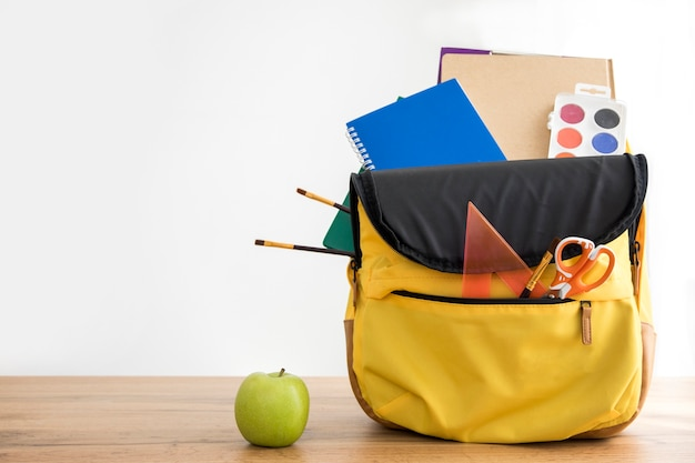 Zaino giallo con materiale scolastico e mela Foto Gratuite