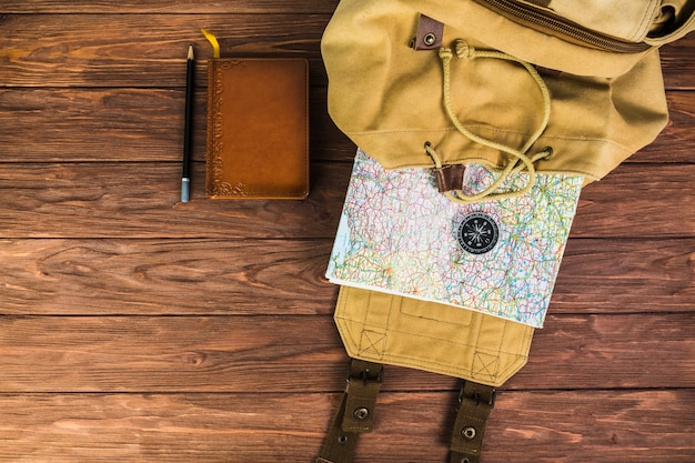 Zaino, mappa e bussola su fondo in legno con diario e penna Foto Gratuite