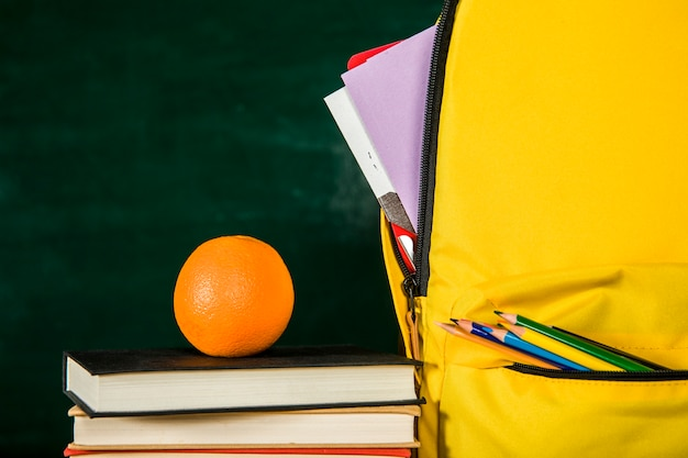 Zaino, pila di libri e arancione Foto Gratuite