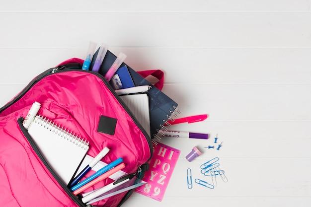 Zaino rosa con vista dall'alto di materiale scolastico Foto Gratuite