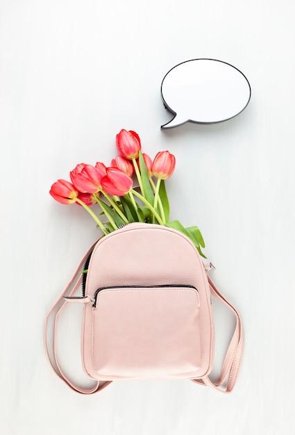 Zaino rosa ragazza lether con tulipani rossi e scatola luminosa a fumetto. Foto Premium