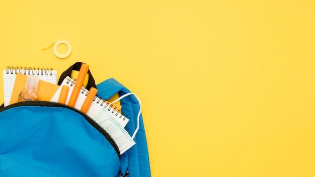 Zaino vista dall'alto con materiale scolastico Foto Gratuite