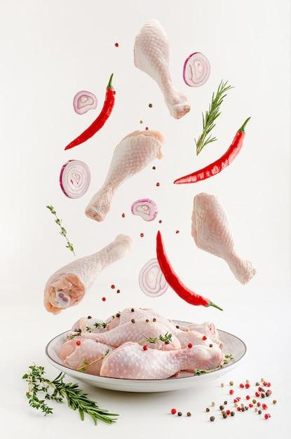 Zampe di pollo crudo marinate piccanti o levitazione di bacchette. concetto di cibo volante. Foto Premium