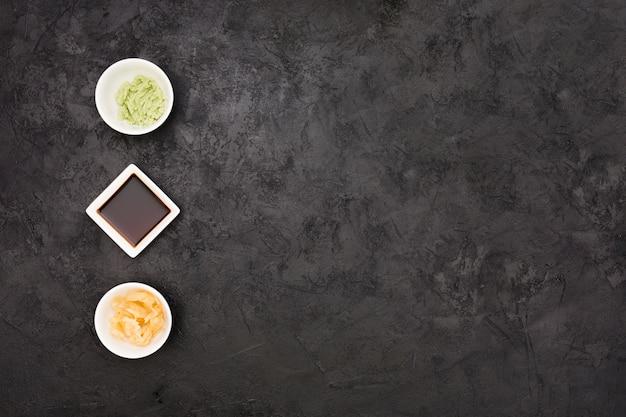 Zenzero marinato; salsa di soia e scodella wasabi disposte in fila sulla superficie nera strutturata Foto Gratuite