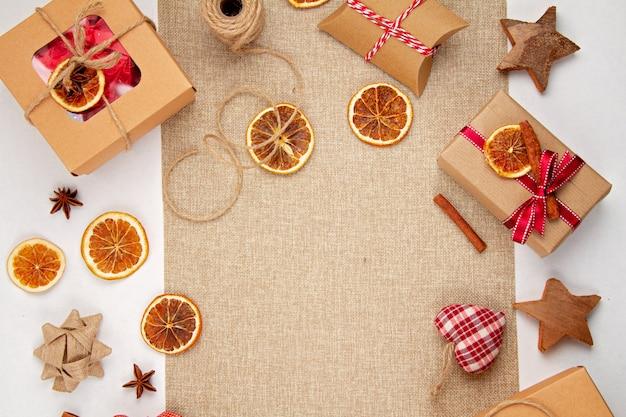 Zero rifiuti natalizi con scatole di cartone artigianali, arance essiccate, decorazioni in legno e tessili, posate piatte in plastica libere Foto Premium
