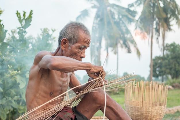 Zio asiatico vecchio con strumenti di vimini. Foto Premium
