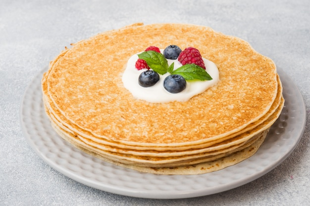 Zolla dei pancake sottili deliziosi con le bacche sulla tabella grigia Foto Premium