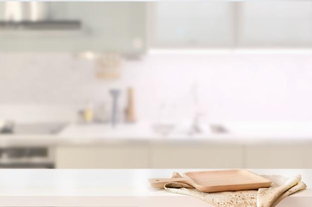 Zolla di legno sulla tabella bianca nella priorità bassa della stanza della cucina e spce della copia Foto Premium
