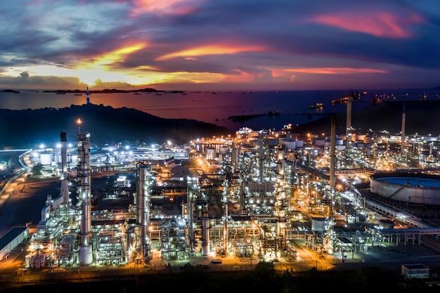 Zona della fabbrica di industria della raffineria di petrolio e del petrolio in tailandia con cielo blu ed il tramonto Foto Premium