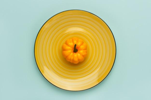 Zucca su un piatto giallo su turchese pastello. Foto Premium