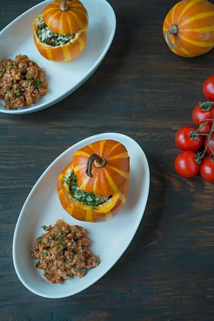 Zucche al forno. piccola zucca ripiena di carne macinata e cosparsa di formaggio. Foto Premium