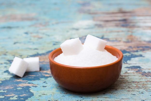 Zucchero granulato e zucchero raffinato in una ciotola su un tavolo di legno Foto Premium