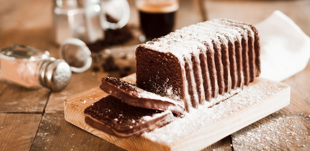 Zucchero spolverato su una fetta di torta sopra il tagliere Foto Gratuite
