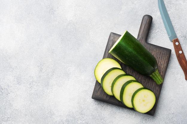 Zucchine verdi fresche tagliate a fette su un tagliere. sfondo grigio cemento. copia spazio. Foto Premium