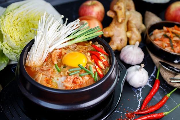 Zuppa di cavolo kimchi in una ciotola con materiali del kimchi su sfondo nero Foto Premium