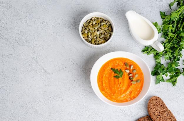 Zuppa di crema autunnale vegetariana di zucche e carote con semi e prezzemolo, piatto laici Foto Premium